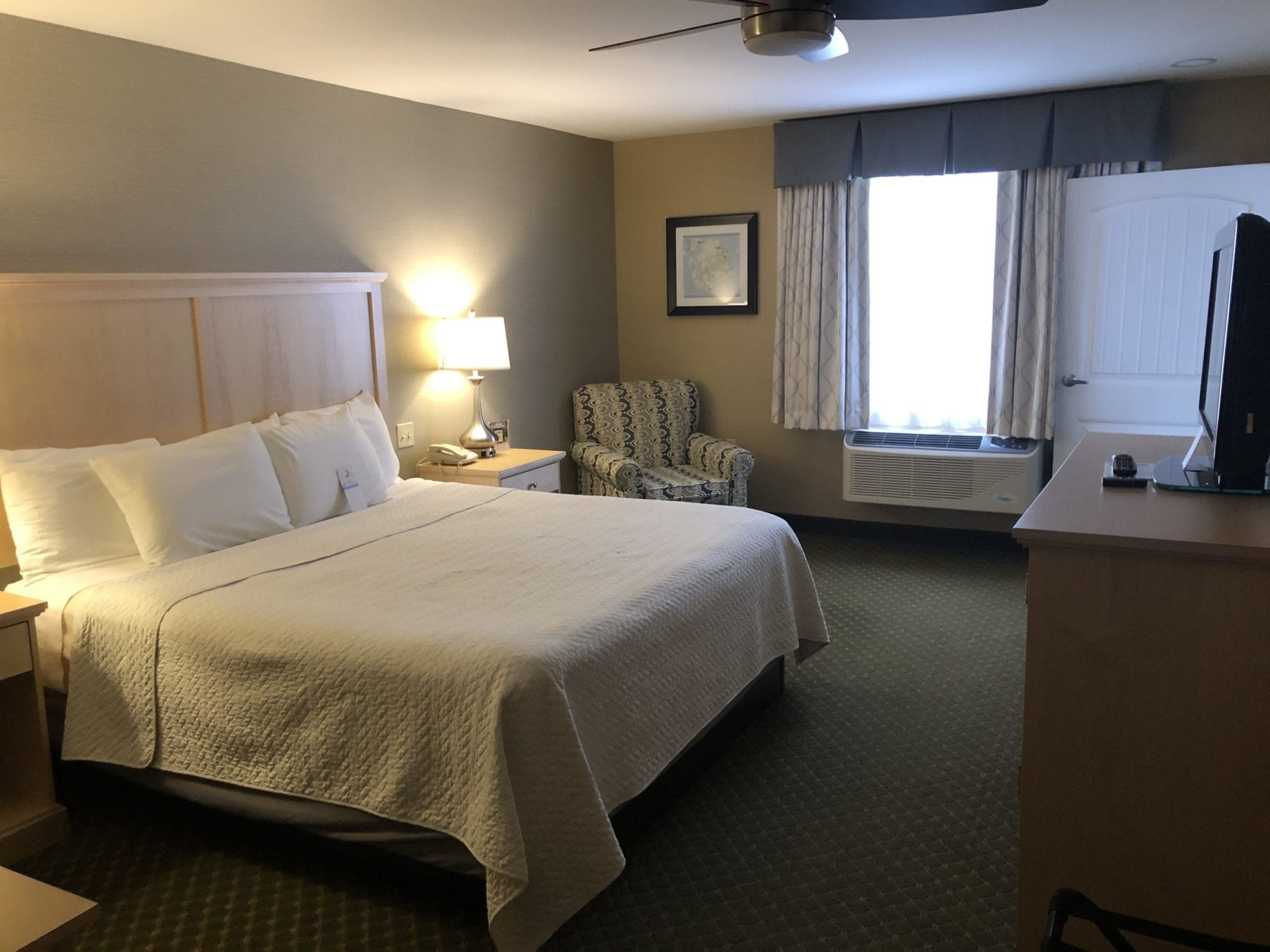 Photo of the bedroom of the Accessible King Suite at the Acadia Inn.