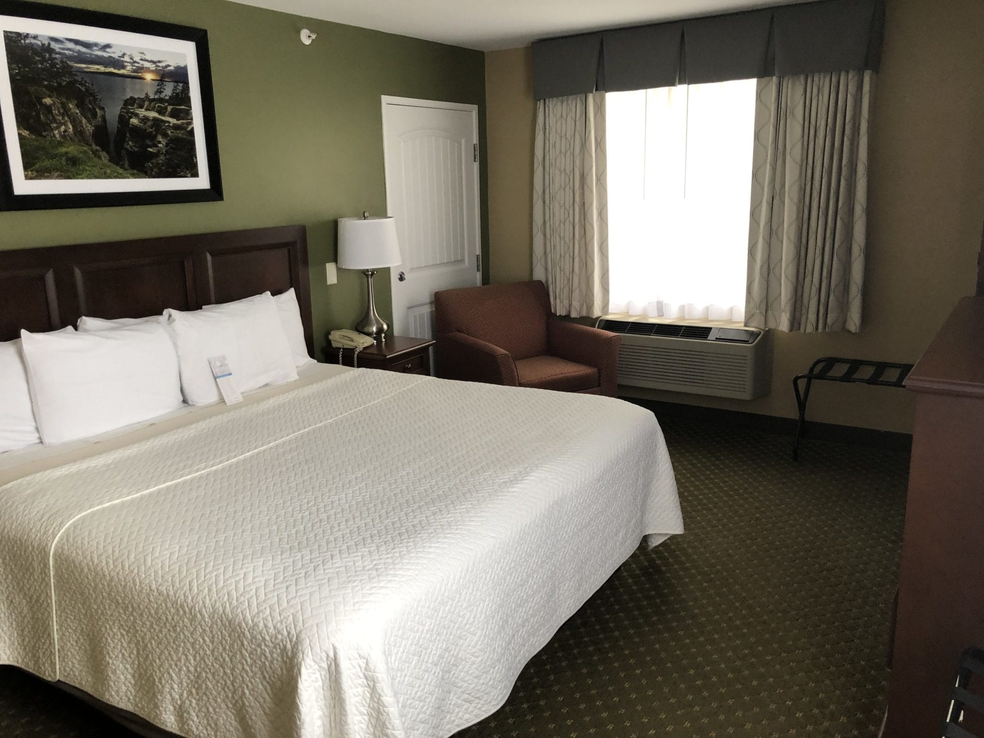 Photo of the bedroom of the Accessible King room with roll-in shower at the Acadia Inn.